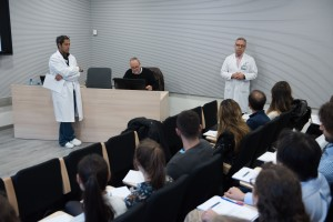 two men in lab coats talking to a room of students