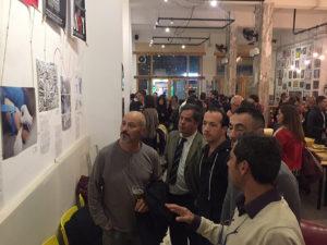 people looking at EAVI2020 photos at Bacanal Café