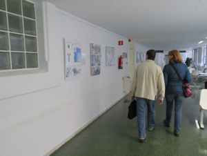 man and a woman walking down a hallway with EAVI2020 photos on the walls