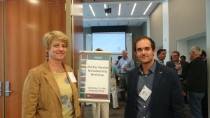 Gabriella Scarlatti and Philip Mundsperger smiling in a room of people, next to a sign for the Vaccine Manufacturing Workshop