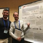Robin Shattock and Yoann Aldon smiling while Robin points at an EAVI2020 scientific poster